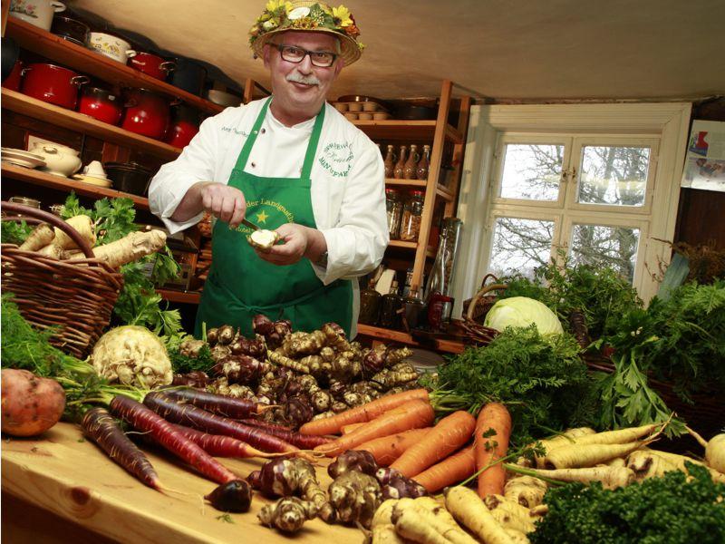 Peter Franke in seiner Kräutermanufaktur mit Kräutern und Gemüse auf dem Arbeitstisch